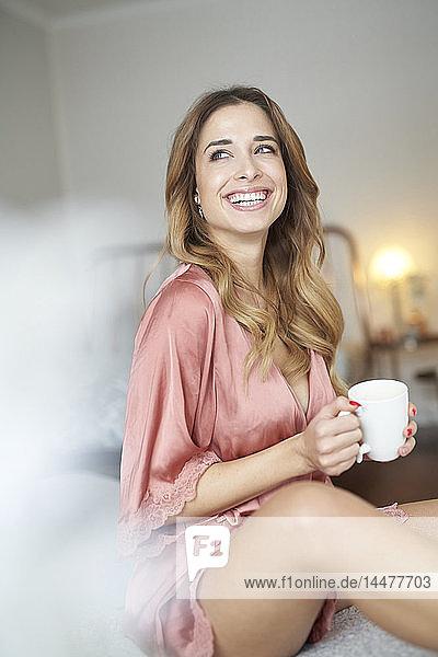 Lächelnde junge Frau im Morgenmantel sitzt mit einer Tasse Kaffee auf dem Bett