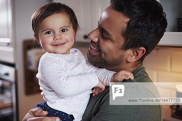 Portrait of smiling father holding baby girl at home