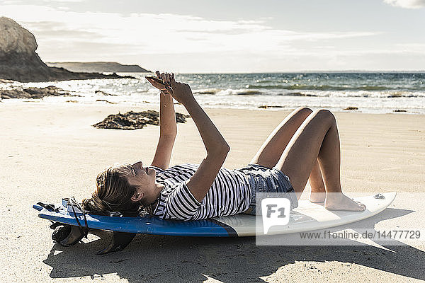 Young woman on the beach  relaxing on surfboard  using smartphone