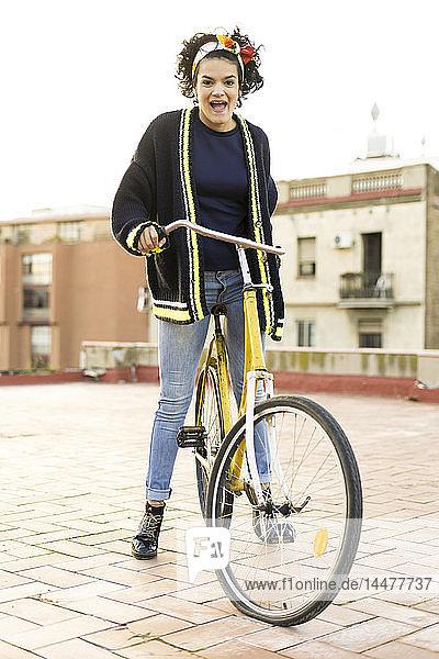 Porträt einer glücklichen jungen Frau mit Fahrrad in der Stadt