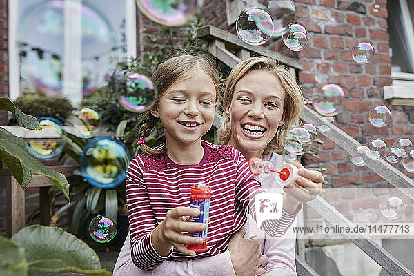Happy mother and daughter making soap bubbles