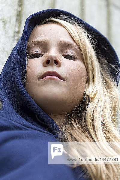 Portrait of serious blond girl wearing blue hooded jacket