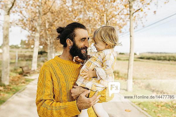 Vater trägt seine Tochter an einem Morgen im Herbst im Park