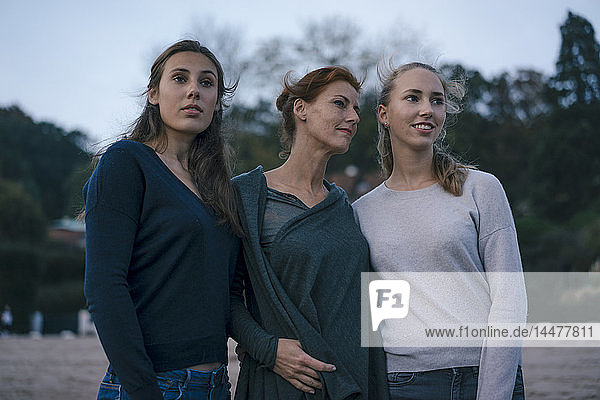 Deutschland  Hamburg  Mutter mit zwei Mädchen im Teenageralter abends am Strand am Elbufer