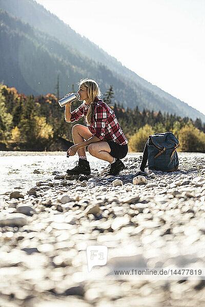Österreich  Alpen  Frau auf Wanderung mit Rast an einem Bach