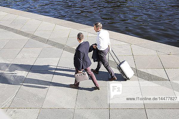 Zwei Geschäftsleute gehen und unterhalten sich am Flussufer