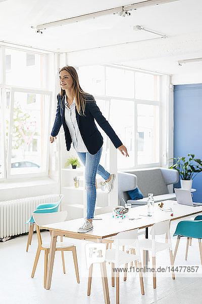 Junge Geschäftsfrau balanciert auf einem Bein auf dem Schreibtisch im Sitzungssaal