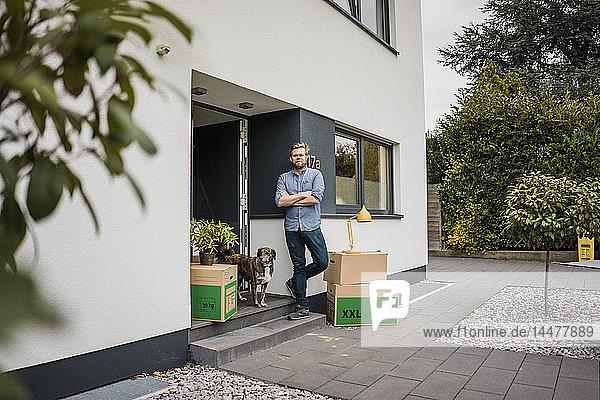Mann mit Hund steht am Hauseingang  umgeben von Pappkartons