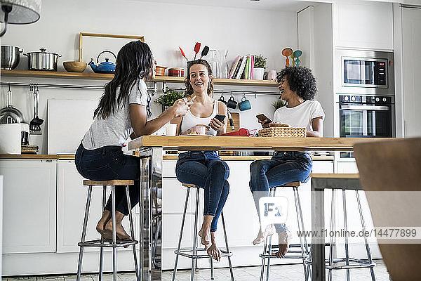 Drei glückliche Frauen sitzen zu Hause am Küchentisch und unterhalten sich