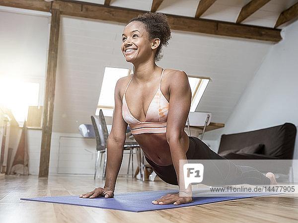 Lächelnde junge Frau  die Yoga praktiziert