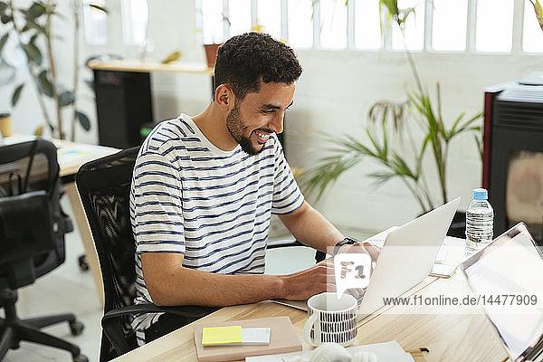 Lächelnder junger Mann mit Laptop am Schreibtisch im Büro