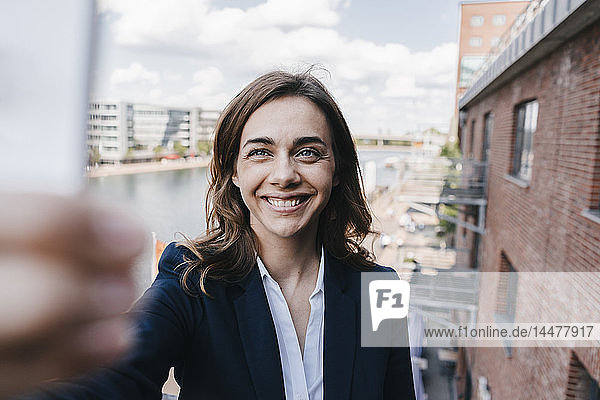 Happy businesswoman taking a smartphone selfie