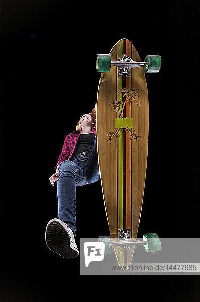 Glückliche junge Frau fährt Longboard von unten gesehen