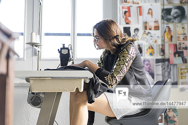 Young designer using sewing machine in her atelier
