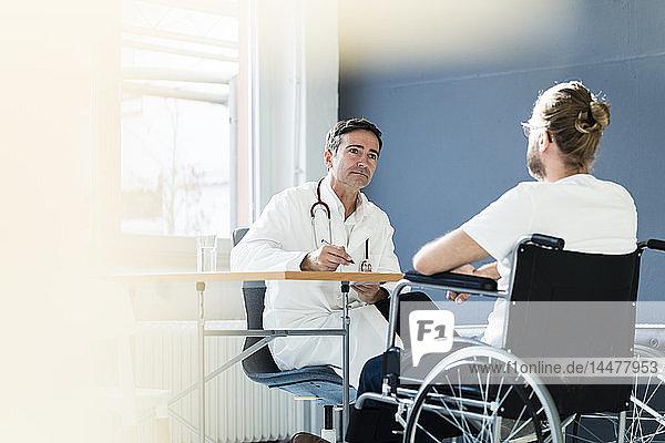 Arzt hört Patient im Rollstuhl in der medizinischen Praxis zu