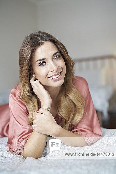 Porträt einer lächelnden jungen Frau im Bademantel im Bett liegend