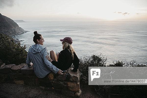 Südafrika  Western Cape  zwei junge Frauen sitzen abends auf einer Mauer und unterhalten sich