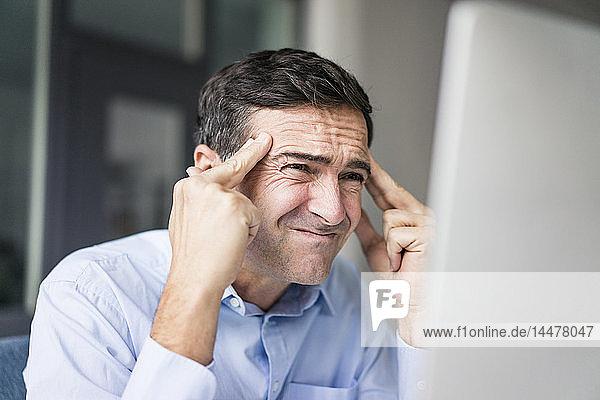 Grimassierender Geschäftsmann schaut auf Computerbildschirm
