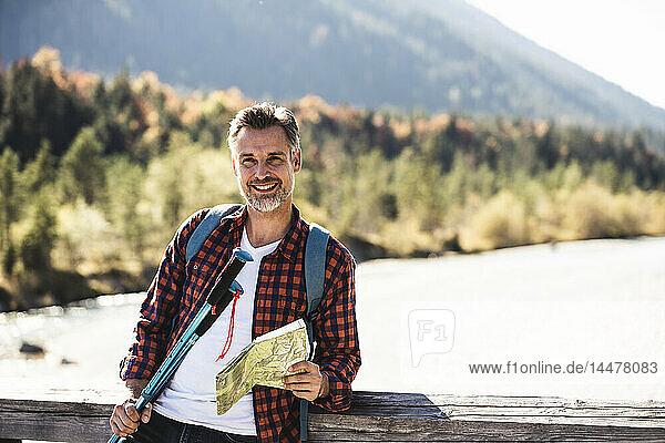 Österreich,  Alpen,  lächelnder Mann auf einer Wanderung mit Karte auf einer Brücke