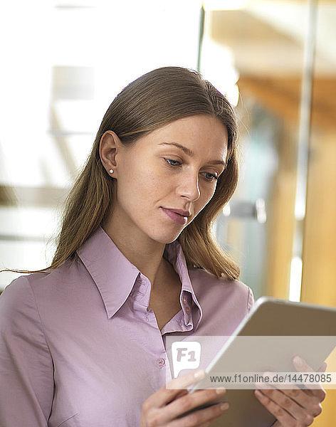 Geschäftsfrau benutzt Tablett im Büro