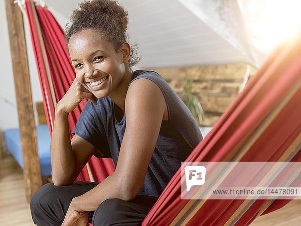 Porträt einer glücklichen jungen Frau in der Hängematte sitzend
