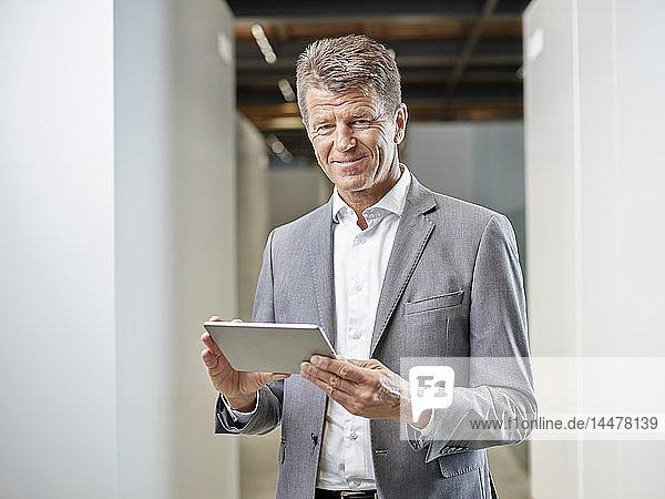 Porträt eines lächelnden Geschäftsmannes mit Tablett auf der Büroetage
