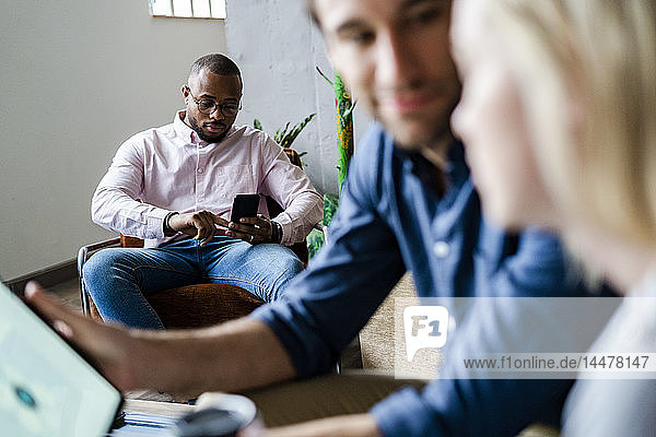 Businessman using cell phone in loft office with colleagues in foreground