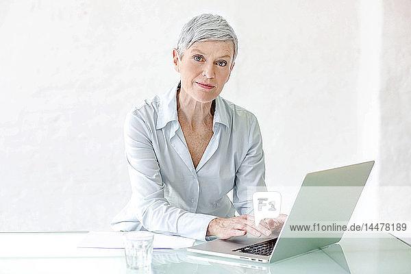 Porträt einer reifen Geschäftsfrau  die am Laptop arbeitet