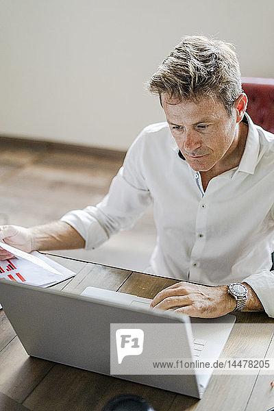 Focused businessman using laptop at desk