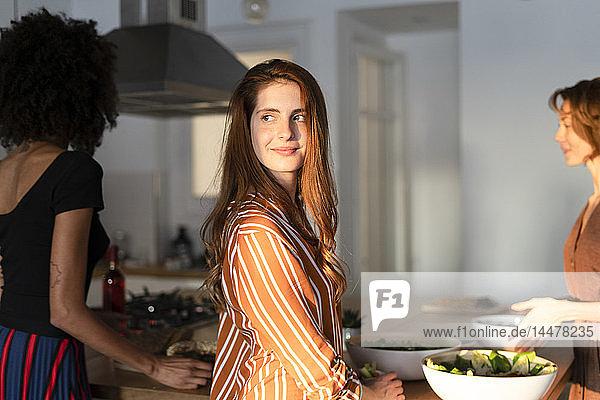 Freunde stehen in der Küche und bereiten eine Dinnerparty vor