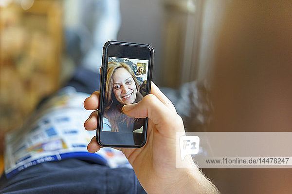 Portrait of happy young woman on display of cell phone skyping with her boyfriend lying on the couch