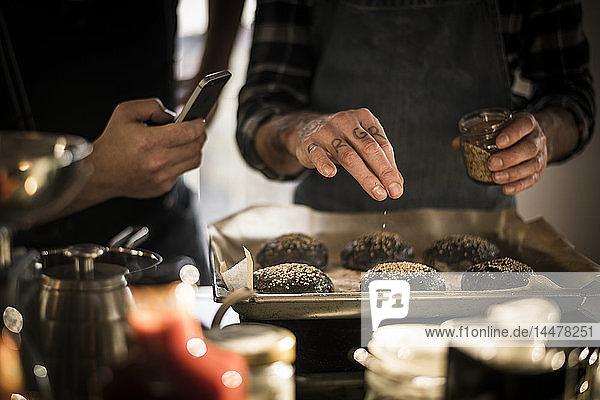 Junger Mann fotografiert einen Freund  der Sesam auf Burgerbrötchen auf einem Backblech streut