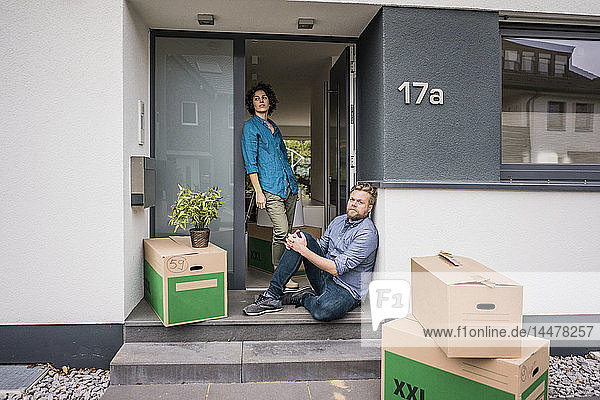 Ehepaar am Hauseingang mit Kartons