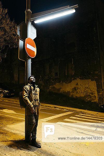 Spain  Igualada  man standing under a street lamp at night