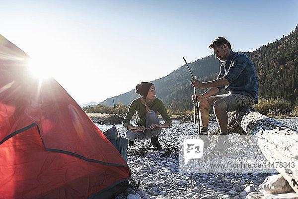Ein erwachsenes Paar zeltet am Flussufer  mit Holz für ein Lagerfeuer