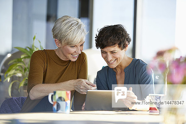 Zwei glückliche Frauen teilen sich die Tablette bei Tisch