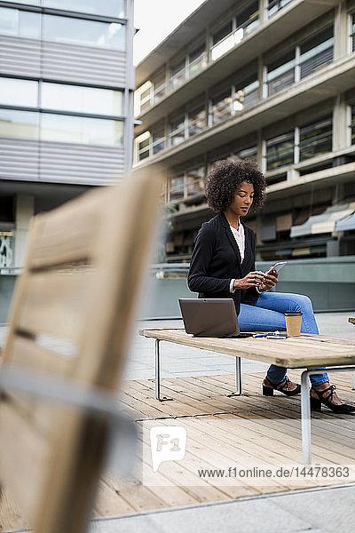 Geschäftsfrau mit Laptop und Kaffee  um auf der Terrasse zu sitzen und sich ein Smartphone anzuschauen