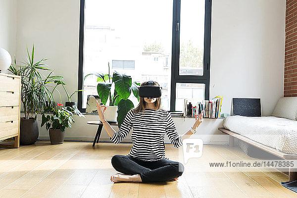 Junge Frau zu Hause mit VR-Brille beim Yoga