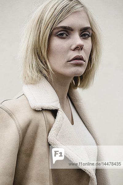 Porträt einer blonden jungen Frau im Mantel
