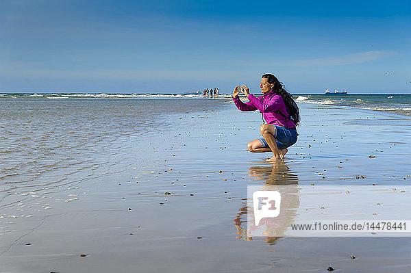 Dänemark  Jütland  Skagen  Grenen  Frau  die Nord- und Ostsee fotografiert