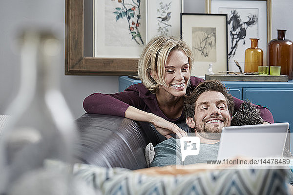 Happy couple with tablet on couch at home