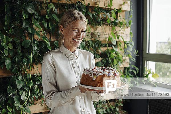 Lächelnde Geschäftsfrau hält Geburtstagskuchen in grünem Büro