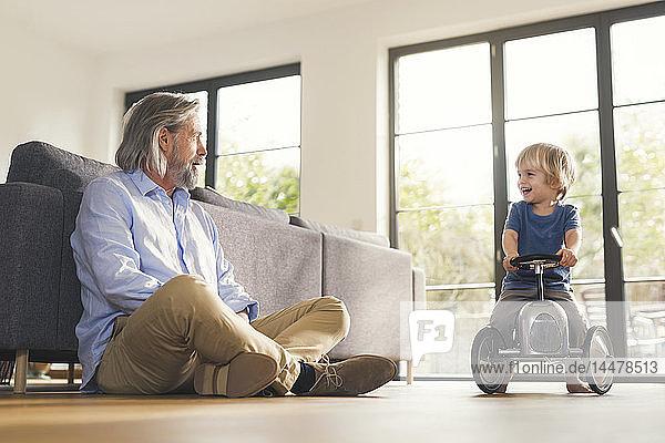 Großvater spielt mit Enkel  sitzt auf Spielzeugauto