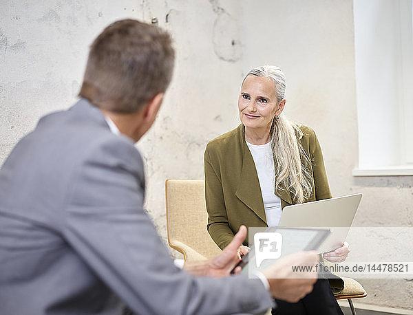 Geschäftsmann und Geschäftsfrau mit Laptop und Tablett im modernen Büro
