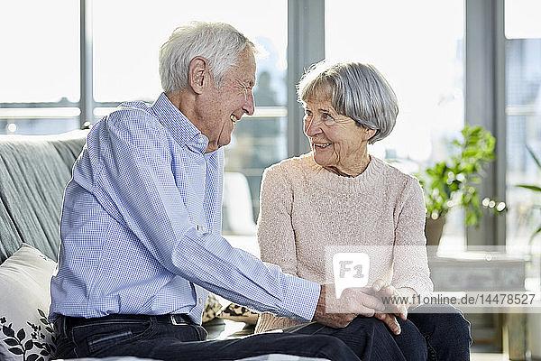 Älteres Ehepaar sitzt auf der Couch und unterhält sich miteinander
