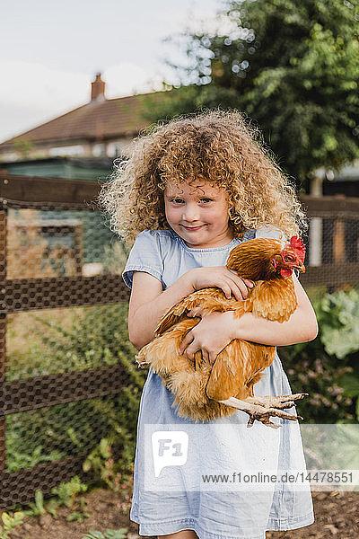 Lächelndes Mädchen umarmt Henne