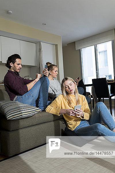 Gelangweilte Freunde sitzen auf der Couch im Wohnzimmer und benutzen digitale Geräte