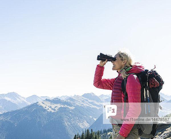 Österreich  Tirol  glückliche Frau  die während einer Wanderung durch ein Fernglas schaut