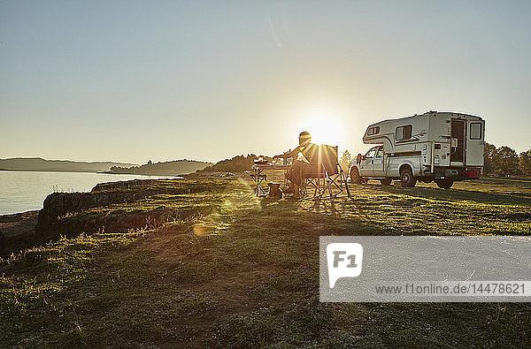 Chile  Talca  Rio Maule  Wohnmobil am See mit Frau und Hund bei Sonnenuntergang