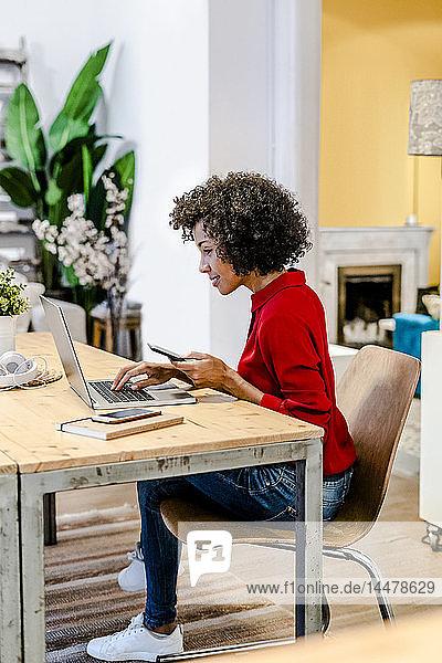Lächelnde Frau mit Laptop und Handy bei Tisch